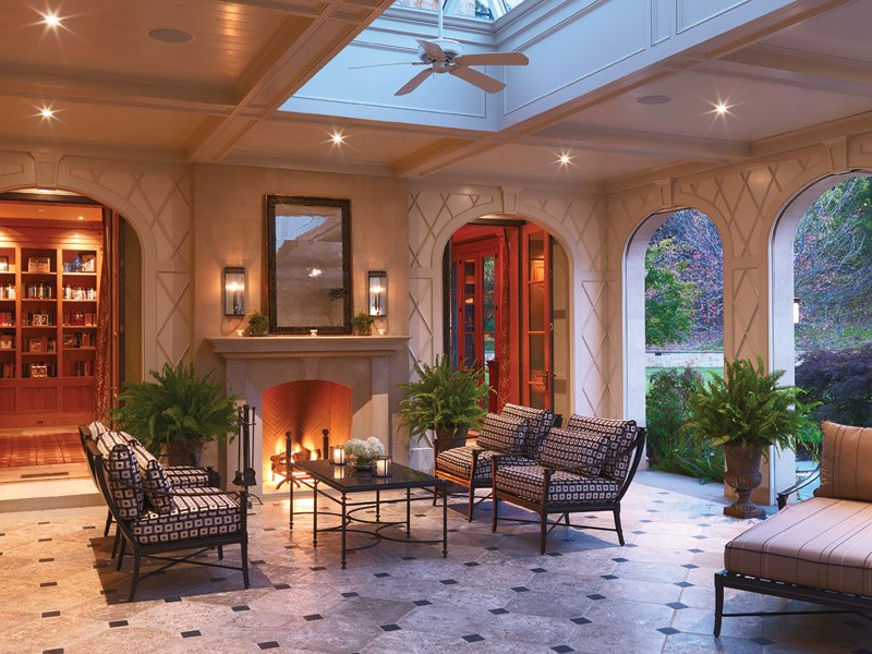 The screened porch includes a fireplace, a signature feature of the architect's designs. Photography by Andrea Hubbell