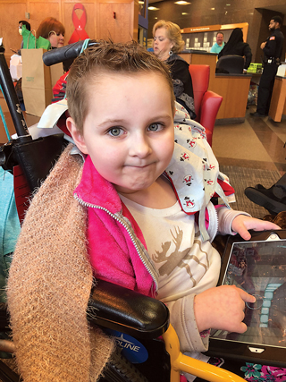 """Between and during tests and treatments, Sawyer has fun with her """"cancer warrior"""" friends and plays on her tablet."""